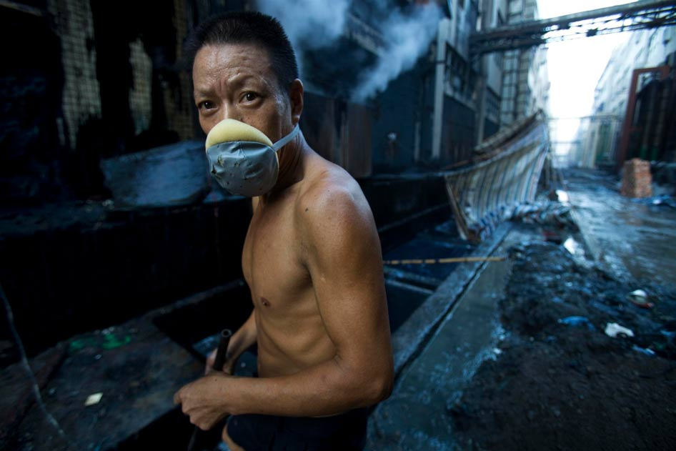 A textile worker washing jeans at a factory in Xintang, China. The high levels of pollution around textile and chemical plants in China are damaging to both workers and the local community. (Photo: Lu Guang / Greenpeace)